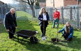 Derbyshire County Council's Cabinet Member for Clean Growth and Regeneration Councillor Tony King (left) helping to plant Chaucer Junior School's Sakura cherry blossom tree with pupils Grace (left) and Charlotte (right) and the school's Community and Gard